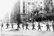 Oddział powstańczy idący zniszczoną ulicą Jasną, fot. Sylwester Braun, Muzeum Powstania Warszawskiego