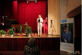 Kobieta ubrana na biało mówiąca do mikrofonu na scenie a za nią kobieta ubrana na różowo