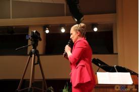 Kobieta w różowym stroju przemawiająca przez mikrofon
