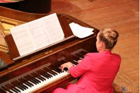 Kobieta w różowym stroju przy brązowym fortepianie