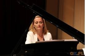 Kobieta ubrana na biało grająca na czarnym fortepianie