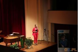 Kobieta ubrana w różowy strój mówi przez mikrofon