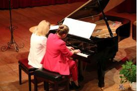 Obie kobiety grające na czarnym fortepianie