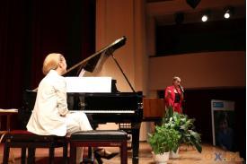 Jedna z kobiet stoi z mikrofonem natomiast druga siedzi przy fortepianie