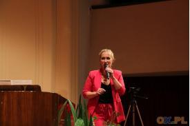 Kobieta w różowym stroju przemawia przez mikrofon