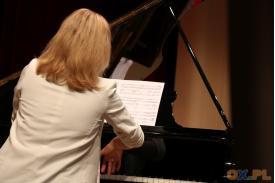 Kobieta ubrana na biało gra na fortepianie