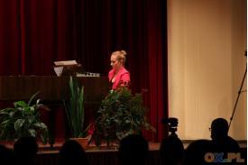 Kobieta w różowym stroju gra na fortepianie