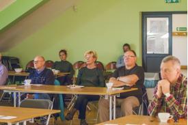 Trójka ludzi oglądających prezentacje a za nimi siedzą dwie młode kobiety