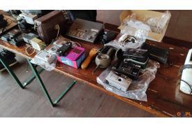 Na stole leżą stare aparaty i różowy telefon
