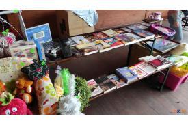 Po lewej i prawej stronie leżą zabawki dla dzieci  a na środku stare książki