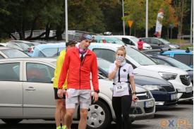 Kobieta uczestnicząca  w biegach oraz dwóch mężczyzn na tle aut