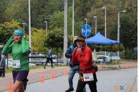 Dwie biegaczki oraz stojący za nimi mężczyzna