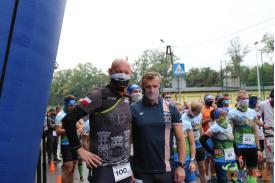 Dwóch mężczyzn pozujących do zdjęcia na tle innych biegaczy