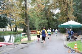 Ludzie podczas biegu, po ich lewej stronie widać rzekę, w po prawej stronie stoliki z parasolami oraz mężczyzna oparty o jeden ze stolików