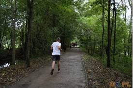 Tył biegnącego mężczyzny na leśnej trasie