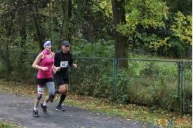 Biegaczka w różowej koszulce z numerem 26 biegnąca z mężczyzną z numerem 92
