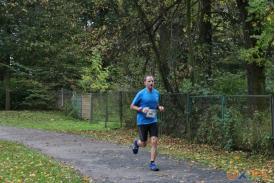 Biegacz  w tle zielony płot
