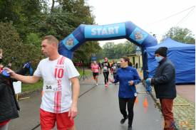 Biegacz w biało czerwonej koszulce z napisem Polska , a za nim kobieta w niebieskiej bluzie trzymająca medal, po jej lewej stronie mężczyzna rozdający medale uczestnikom