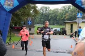 Biegacz przebiegający przez metę i patrzący na zegarek, a obok niego kobieta w czarnej czapce i różowej bluzie