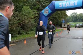 Dwójka mężczyzn ubranych na czarno przechodzą przez mete , pierwszy mężczyzna trzyma lewą dłoń na ustach, za nimi widać mężczyznę biegnącego do mety