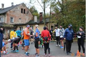 Grupa biegaczy po biegu, mająca na szyi medale, za nimi stoi stary budynek