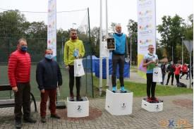 3 Mężczyzn stojąca na podium obok jedno z nich stoi organizator