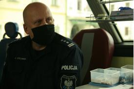 Policjant w mundurze w maseczce czekający na pobranie krwi