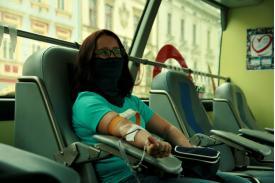 Siedząca kobieta w maseczce która ma pobieraną krew