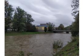 Przybierająca rzeka na przeciw żółty budynek i most