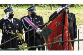 Troje strażaków trzymających sztandar