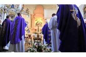 Księża modlący się przy trumnie