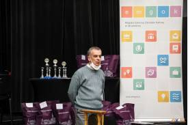 Mężczyzna przemawiający w tle nagrody oraz puchary