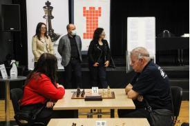 Młoda kobieta z mężczyzną siedząca przy stoliku z planszą do gry w szachy ,w t;e dwie kobiety oraz mężczyzna w maseczkach