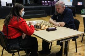 Młoda kobieta grająca w szachy z mężczyzną