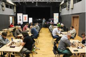 Grupy mężczyzn siedzących w osobnych stolikach grających w szachy