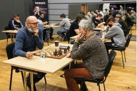 Dwoje mężczyzn skupiających się na grze w tle ,rozgrywające się turnieje