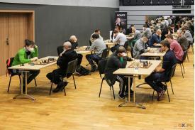 Grupa mężczyzn siedząca przy stolikach rozgrywająca turniej  gry w szachy