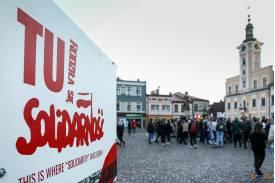 """Baner z napisem """"TU RODZIŁA SIĘ SOLIDARNOŚĆ""""  w tle grupa protestujących"""