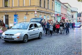 Srebrne auto w tle protestujący idący za autem