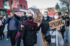 """Kobieta trzymająca baner z napisem """"TO JEST WOJNA"""" w tle pozostali protestujący"""