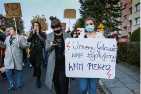 """Kobieta trzymająca baner z napisem """"UMIEMY GOTOWAĆ WIĘC ZAGOTUJEMY WAM PIEKŁO"""""""