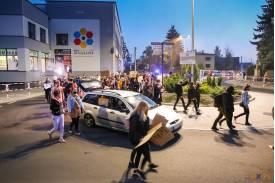 Maszerujący protestujący trzymające banery   w tle srebrny samochód