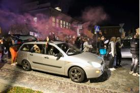 Srebrne auto a w nim młodzi ludzie którzy protestują
