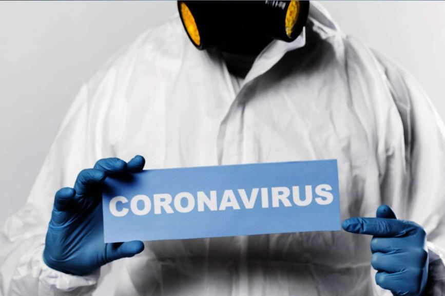 Osoba w masce w białym fartuchu trzymająca kartkę z napisem CORONAVIRUS