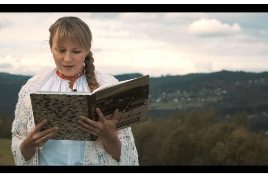 Anna Guzik w stroju beskidzkim  na tle gór czyta utwór literacki dotyczący gminy Istebna