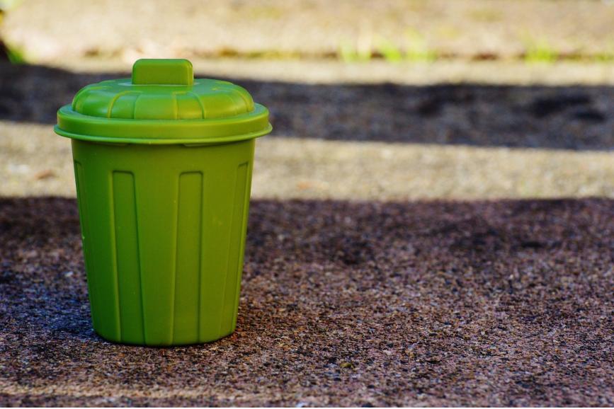 Zielony kosz na śmieci, stojący  na drodze