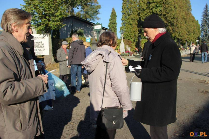 Mężczyzna zbierający datki, ubrany na czarno i dwie starsze kobiety na cmentarzu