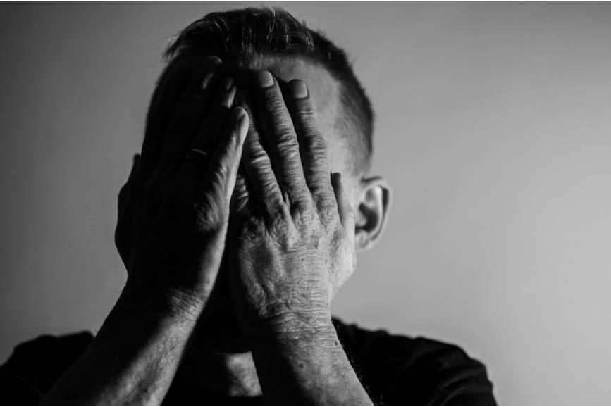 Czarno białe zdjęcie mężczyzny z rękami zakrywającymi twarz