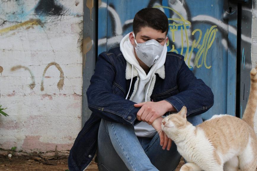 Mężczyzna siedzący na ulicy w maseczce, głaszczący rudego kota