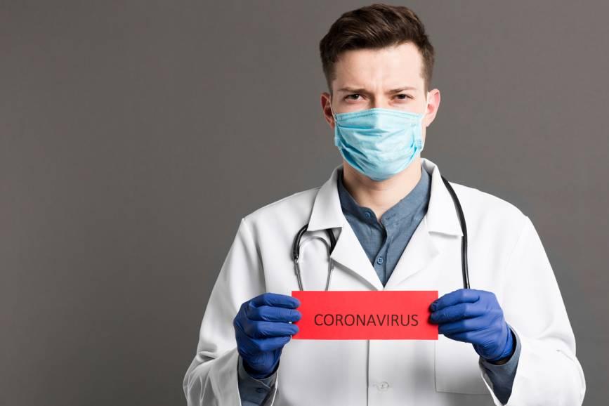 Mężczyzna w stroju lekarza w maseczce , trzymający kartkę z napisem CORONAVIRUS